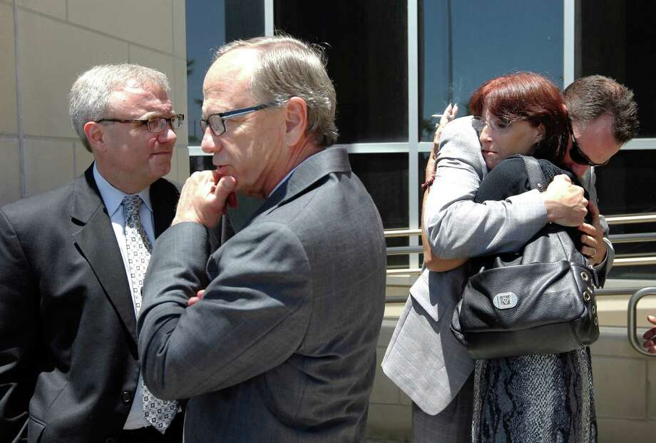 Deborah Ray Holst hugs Prosecutor Clint Woods on Tuesday May 7, 2013, in Galveston, Texas,  after he and Prosecutors Pat Knauth, left, and Ed Shettle spoke to members of the media outside the Galveston County Courthouse.  Bartholomew Granger Sr. was sentenced to death Tuesday  for the 2012 shooting outside the Jefferson County Courthouse that killed Holst's mother, Minnie Ray Sebolt, and injured three others. (AP Photo/The Galveston County Daily News,Jennifer Reynolds) Photo: Jennifer Reynolds, MBR / The Galveston County Daily News