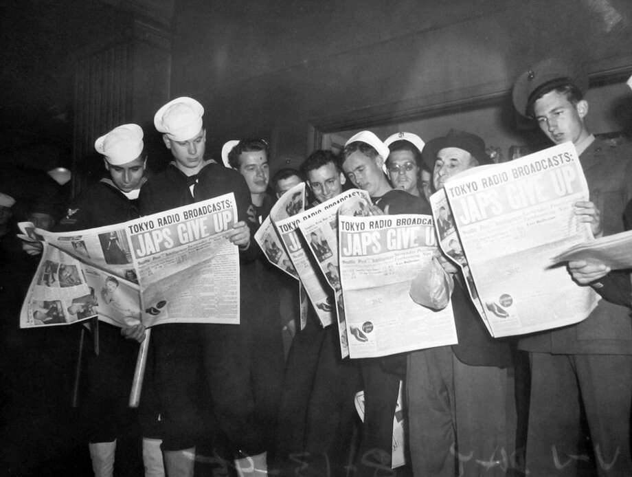 This image, said to have been taken on Aug. 13, 1945, shows sailors reading news of Japan's surrender. It's not clear exactly where it was taken – P-I photographers notes were not saved other than the negative sleeve - but it's believed to have been along Fourth Avenue. Photo: Copyright MOHAI,  Seattle Post-Intelligencer Collection,  PI28288