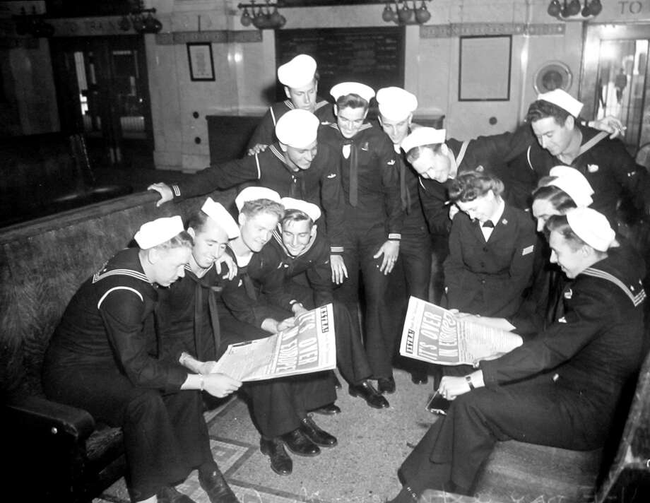 Sailors gather at King Street Station to read an Aug. 1945 Seattle Post-Intelligencer, announcing a victory in Europe. King Street Station completed a multi-million-dollar restoration last month, so the space now looks much like it did that day. Photo: Copyright MOHAI, Seattle Post-Intelligencer Collection, PI28287