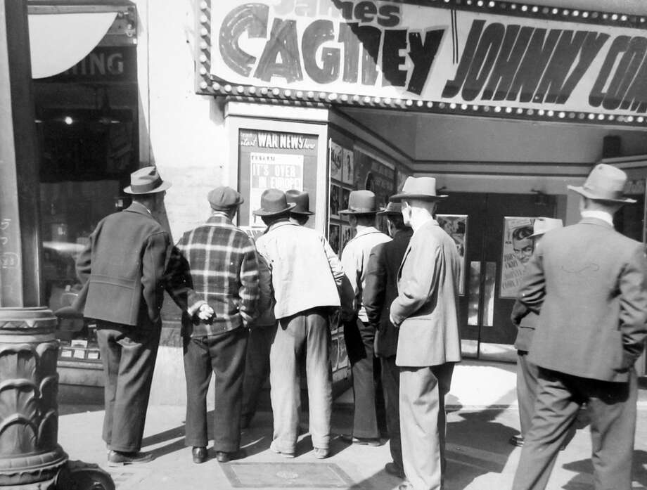 This group of men gathered on May 5, 1945 to read an extra edition of the Seattle Post-Intelligencer posted at a movie theatre near Second Avenue and Washington Street, according to the sleeve that holds this negative. The image has not previously been published. Photo: Copyright MOHAI, Seattle Post-Intelligencer Collection, PI28284