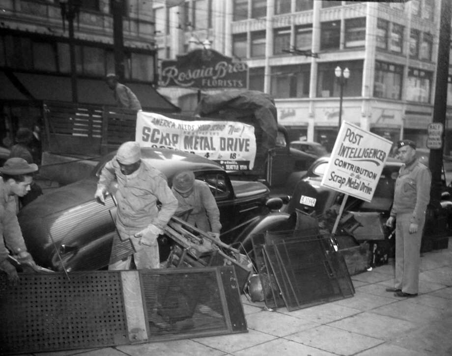Here's another previously unpublished image from the P-I scrap metal drive in Oct. 1944. The location was not recorded, but you could find it by searching city directories for Rosaia Brothers Florists, shown in the back. The Seattle Public Library's Seattle Room has old city directories in their collection – including some available online. Photo: Copyright MOHAI, Seattle Post-Intelligencer Collection, PI28158