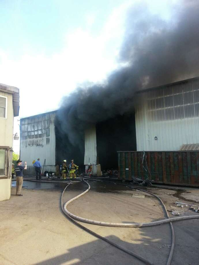Smoke spills out of a building in Shelton during a fire Tuesday afternoon. Photo: Contributed Photo