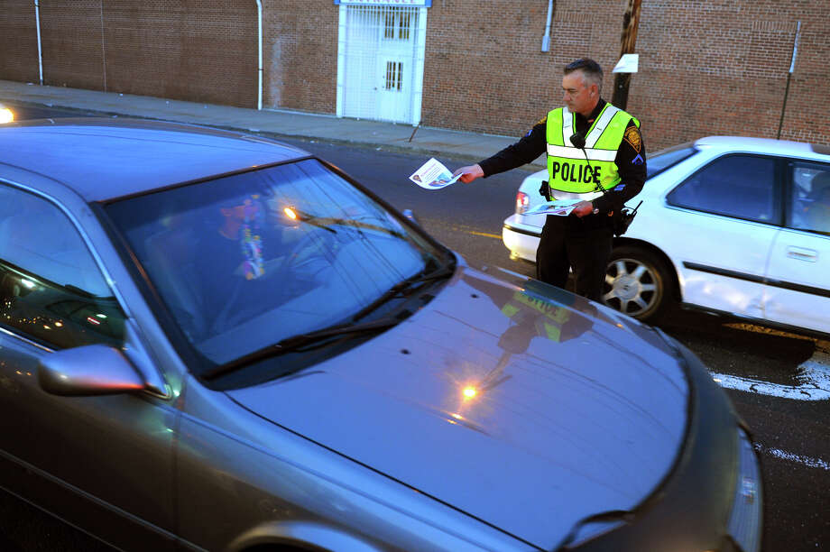 Bridgeport Police Officer Brian Pisanelli hands out flyers at a checkpoint at the intersections of Main Street and Capitol Avenue in Bridgeport, Conn. on Tuesday May 7, 2013. The department is looking for help from the public along this busy intersection for information which may lead to who is responsible for last week's hit-and-run accident along Capitol Avenue which left a two year old boy in critical condition. Photo: Christian Abraham / Connecticut Post
