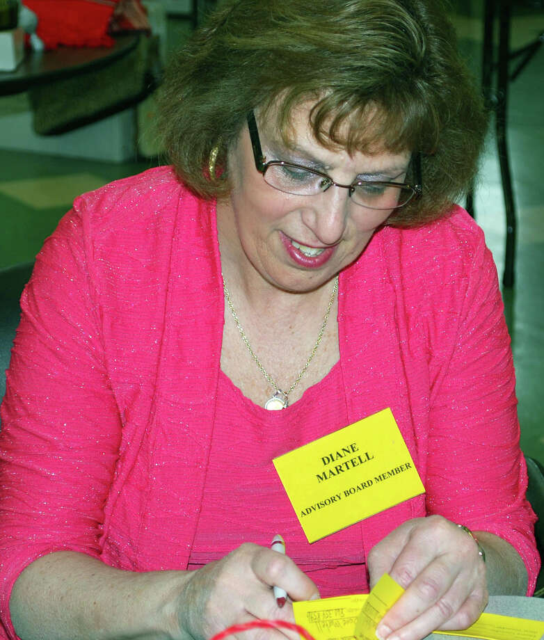 Diane Martell, a member of the advisory board at the New Milford Senior Center, fills out an entry slip for the penny auction offered at an April 19-20, 2013 tag and bake sale organized by the advisory board Photo: Deborah Rose