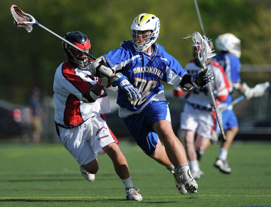 Brookfield's Dane Heckmann, right, races around New Fairfield defender John Gephart during New Fairfield's 15-12 win over Brookfield at New Fairfield High School in New Fairfield, Conn. on Tuesday, May 7, 2013. Photo: Tyler Sizemore / The News-Times