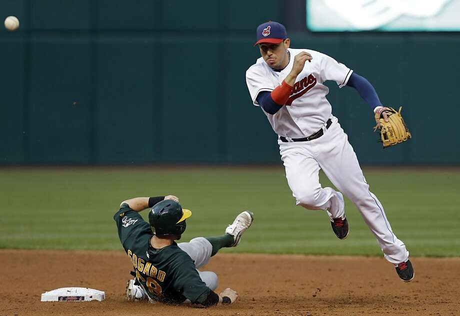 Cleveland Indians shortstop Asdrubal Cabrera throws over Oakland Athletics' Eric Sogard to complete a double play on Michael Taylor in the third inning of a baseball game Tuesday, May 7, 2013, in Cleveland. (AP Photo/Mark Duncan) Photo: Mark Duncan, Associated Press