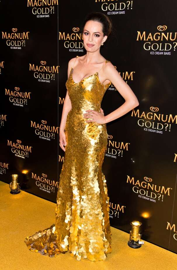 "Actress Caroline Correa poses wearing a Zac Posen one-of-a-kind 24k gold dress valued at $1.5 million at the premiere of ""As Good As Gold"" during the 2013 Tribeca Film Festival at Gotham Hall on April 18, 2013 in New York City."