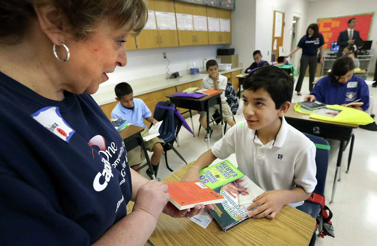 Barbara Knapik of Capital One Bank presents five books to Daniel Hernandez, a fifth-grader grader at Rodriguez Elementary School, so he can start his private library at home.
