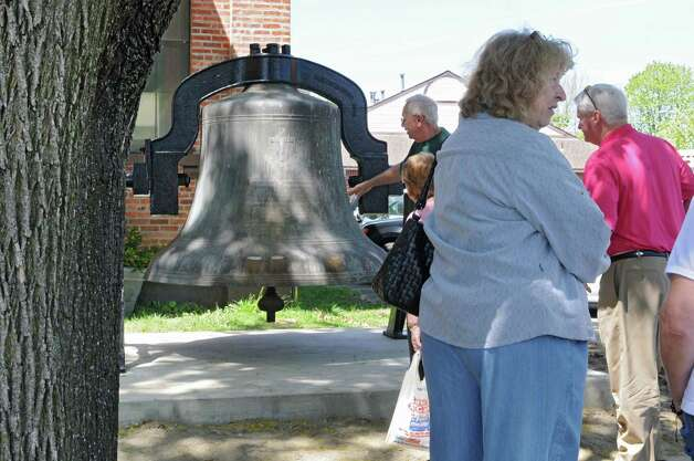 A small crowd of people gather to look at the bell from St. Patrick's Church which is on display in front of the Watervliet Historical Society Museum on Tuesday, May 7, 2013 in Watervliet, N.Y. The over 7000 pound bell was cast in 1906 at Meneely & Co. which used to be just across the street from this museum. (Lori Van Buren / Times Union) Photo: Lori Van Buren / 10022286A