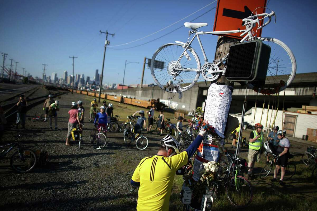 Mourner Lars Halstron places his hand on a memorial and bows his head during a bike ride in honor of Lance David, a cyclist killed in an accident with a semi-truck on East Marginal Way South near South Hanford Street in Seattle. David, 54, was riding his bike May 1st from Federal Way on the first day of Bike to Work Month when he died. Photographed on May 4, 2013.