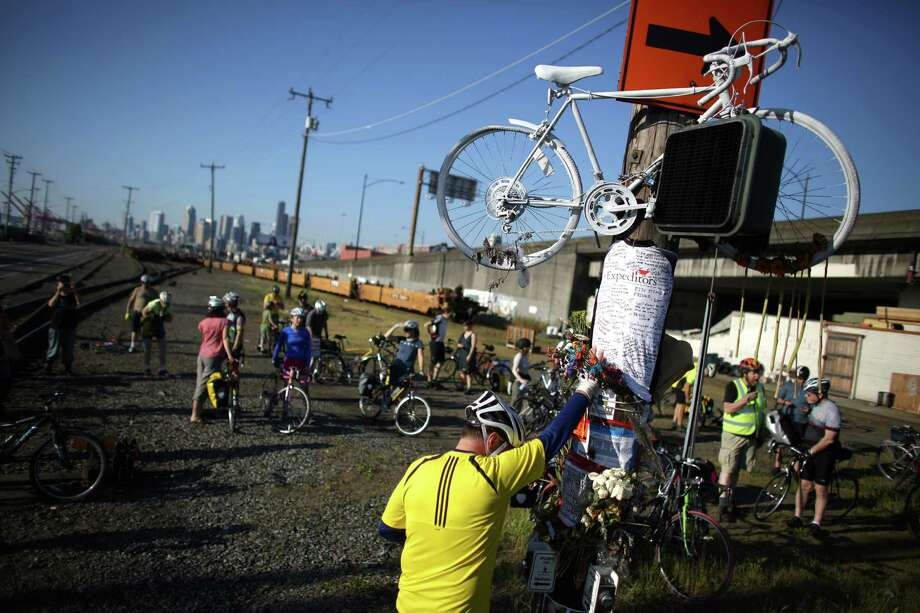 Mourner Lars Halstron places his hand on a memorial and bows his head during a bike ride in honor of Lance David, a cyclist killed in an accident with a semi-truck on East Marginal Way South near South Hanford Street in Seattle. David, 54, was riding his bike May 1st from Federal Way on the first day of Bike to Work Month when he died. Photographed on May 4, 2013. Photo: JOSHUA TRUJILLO, SEATTLEPI.COM / SEATTLEPI.COM