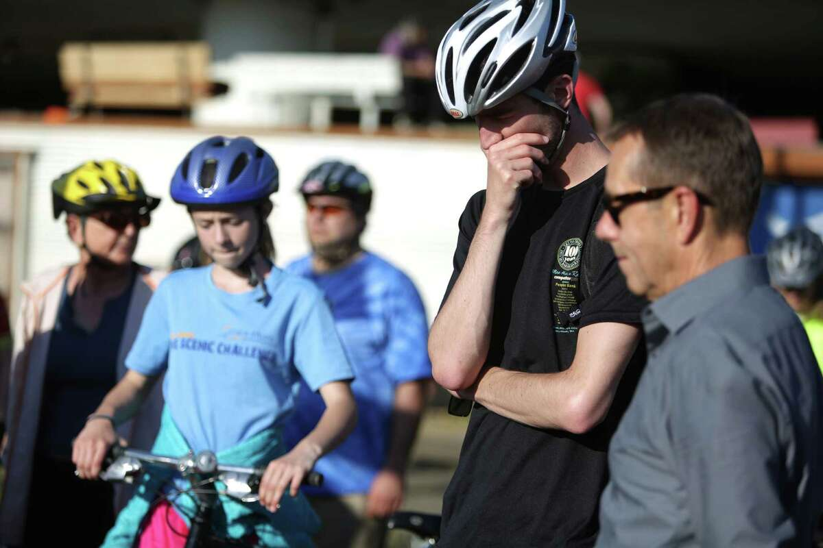 People bow their heads during a memorial bike ride for Lance David, a cyclist killed in an accident with a semi-truck on East Marginal Way South.