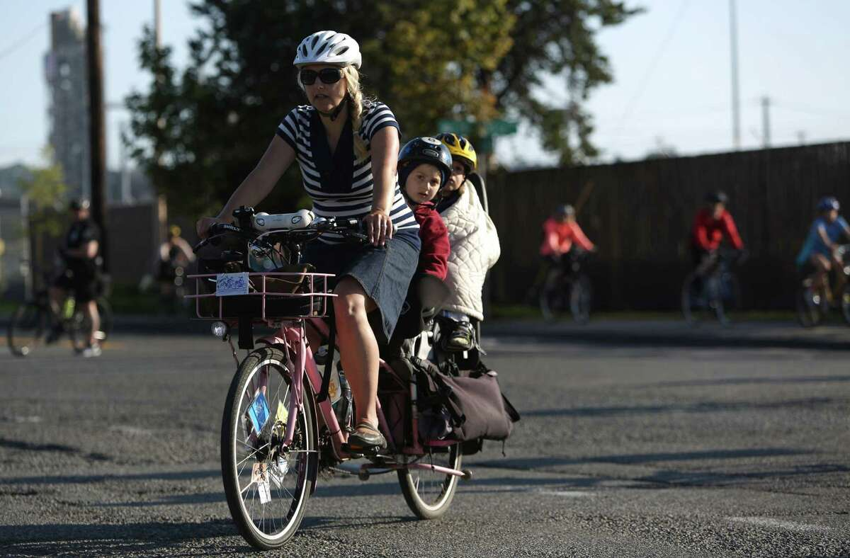 Madi Carlson rides with her sons Brandt, 6, and Rijder, 3, during a memorial bike ride for Lance David, a cyclist killed in an accident with a semi-truck.