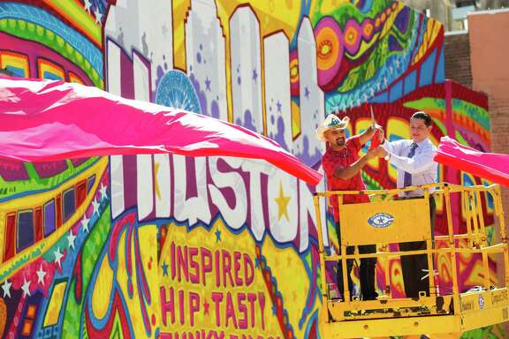 "Artist GONZO247, left, and City Council member James Rodriguez cuts a giant red ribbon to unveil his mural ""Houston Is"" during the kickoff of ""Houston Is Inspired"" campaign Tuesday, May 7, 2013, in Houston. GONZO247 said he spent a month working on the mural, using 250 cans of spray paint.  ( Brett Coomer / Houston Chronicle )"