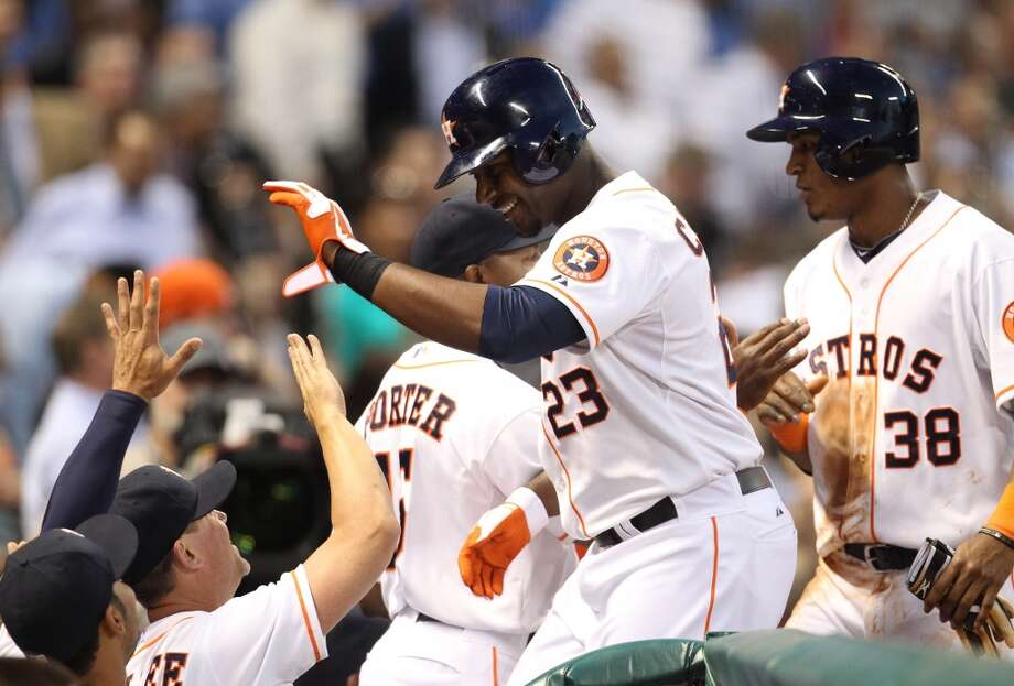 Chris Carter of the Astros is congratulated by teammates after hitting a home run during the third inning. Photo: Karen Warren, Houston Chronicle