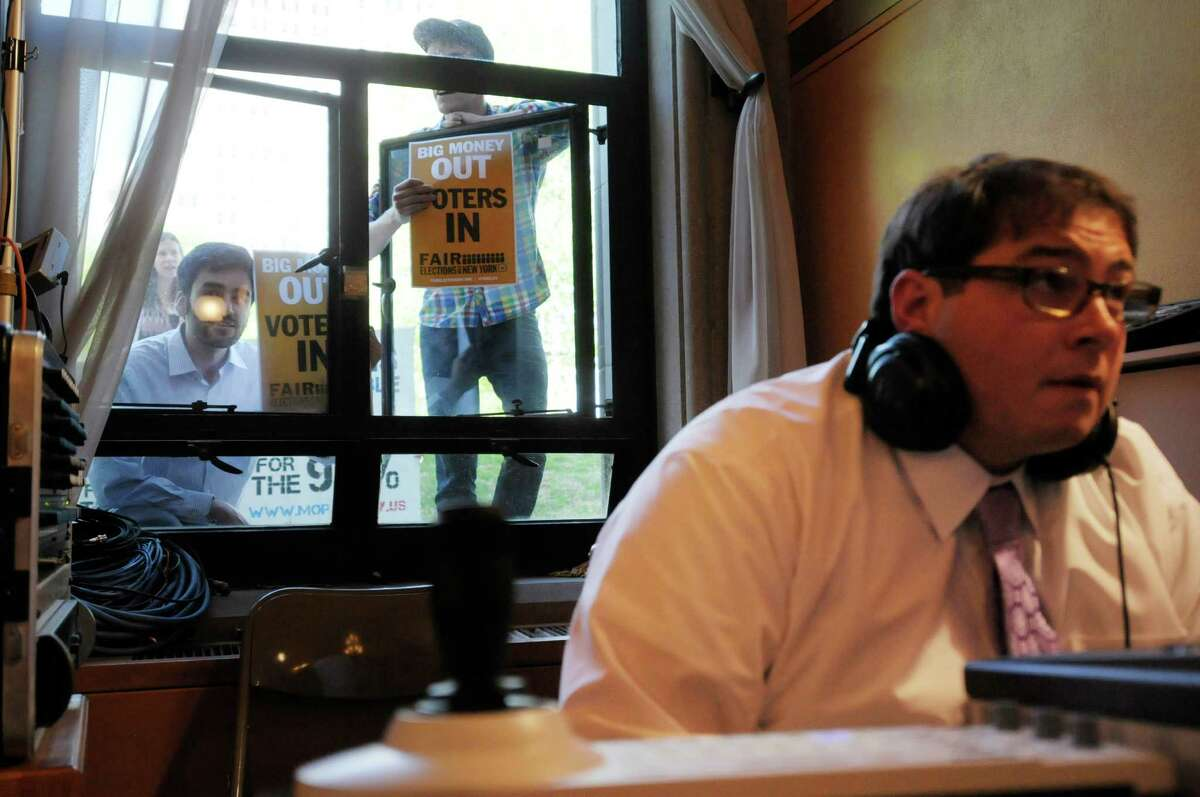 A audio technician works in the foreground as protestors chant from an open window during a legislative hearing on public financing in New York City elections at the Capitol on Tuesday, May 7, 2013 in Albany, NY. The windows were then closed by Capitol staff because the chanting was disrupting the hearing. (Paul Buckowski / Times Union)