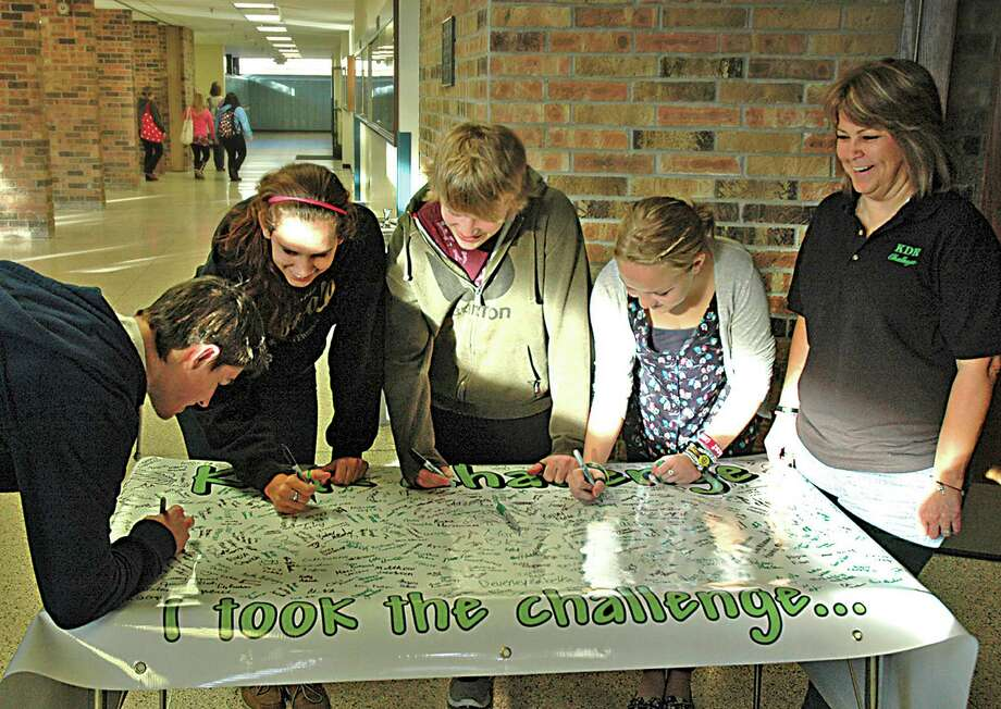 "FILE - This Nov. 3, 2011 file photo shows, from left, Brock Raffaele of Cadillac, Mich. and Sault High students Lauren Gee, Conner Langendorf, and Emma Harrington, taking the KDR Challenge and sign the banner as speaker Bonnie Raffaele, right, watches in Sault Ste. Marie, Mich.. Seventeen-year-old Kelsey Raffaele's last words were over a cell phone to a friend: ""I'm going to crash!"" The car she was driving had clipped a snow bank and spun into oncoming traffic, where it was t-boned by an SUV. She died at a hospital without regaining consciousness. Police chalked the accident up to mistakes made by a novice driver, unaware that she had been on the phone at the time.(AP Photo/The Evening News, Mike McKee) Photo: Mike McKee"