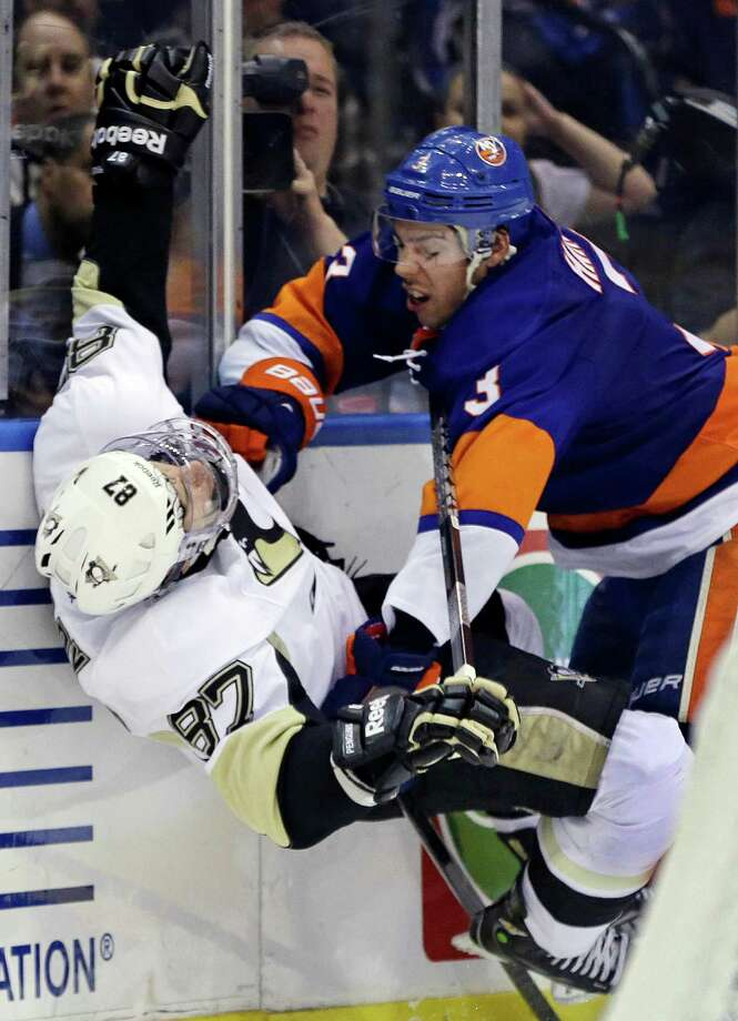 New York Islanders defenseman Travis Hamonic (3) checks Pittsburgh Penguins center Sidney Crosby (87) in the third period of Game 4 of their first-round NHL hockey Stanley Cup playoffs hockey series at Nassau Coliseum in Uniondale, N.Y., Tuesday, May 7, 2013. The Islanders won 6-4. (AP Photo/Kathy Willens) Photo: Kathy Willens