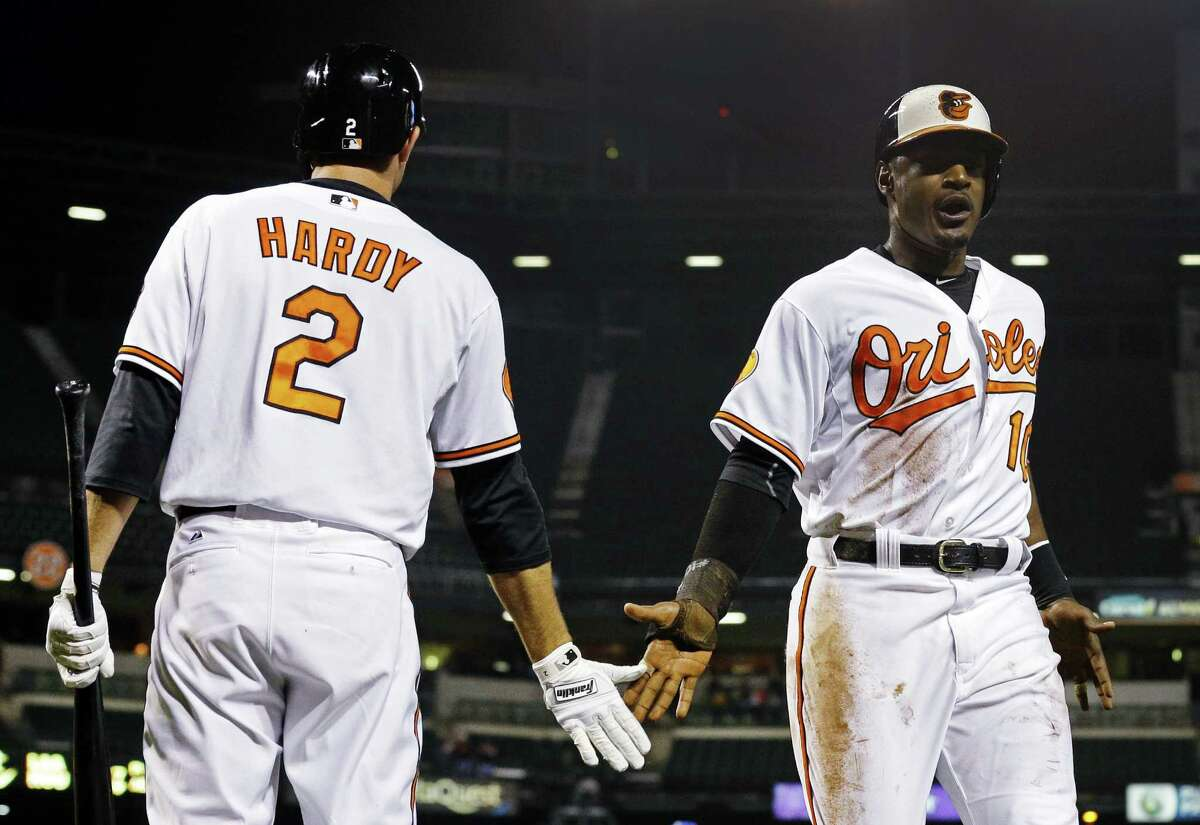 Baltimore's Adam Jones (right) is greeted by teammate J.J. Hardy after scoring in the eighth.