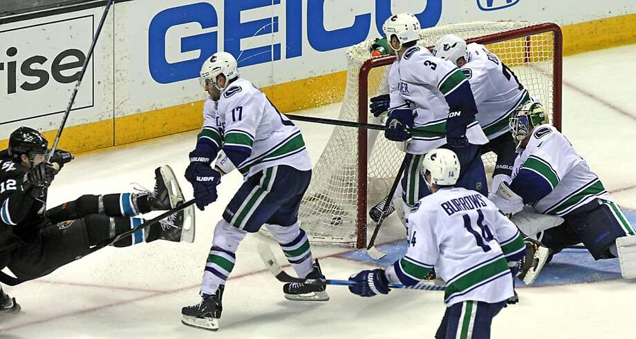 Patrick Marleau (12) of the San Jose Sharks gets knocked down after scoring the winning goal in the fourth period of their NHL play-off game with the Vancouver Canucks at HP Pavilion on Tuesday, May 7, 2013 in San Jose, California. Photo: Lance Iversen, The Chronicle