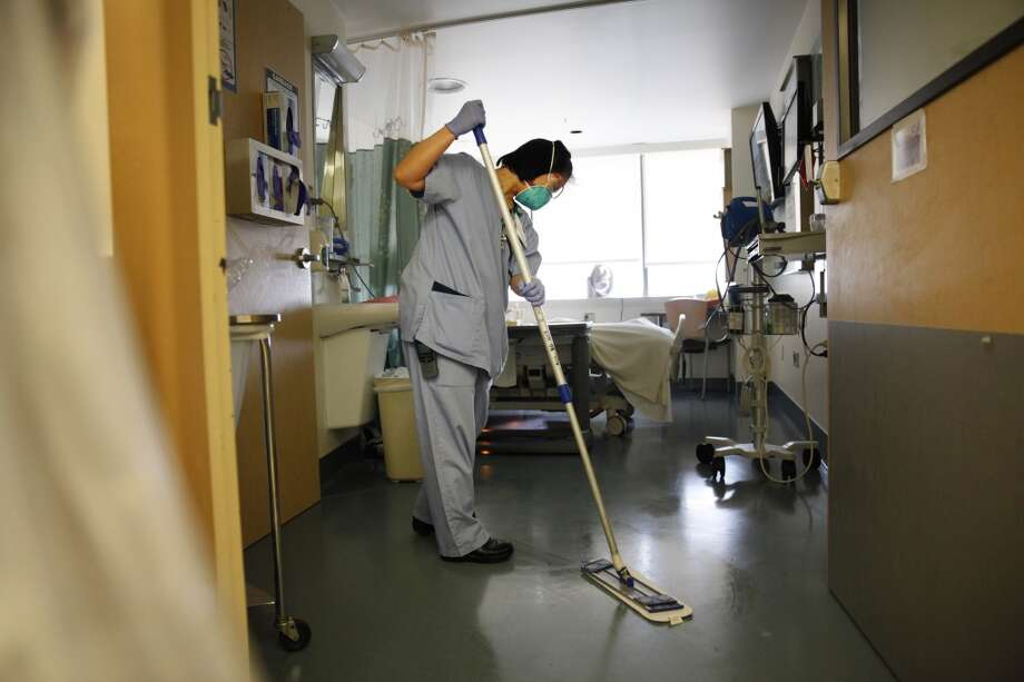 Qianyi Lei, patient support assistant, uses a microfiber mop while cleaning a hospital room at UCSF Long Hospital on Monday, May 6, 2013 in San Francisco, Calif.