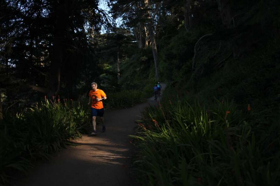 A runner passes through a shaft of light on a trail between Eagles Point and Dead Man's Point on May 2, 2013 in the Lincoln Heights area of San Francisco, Calif.