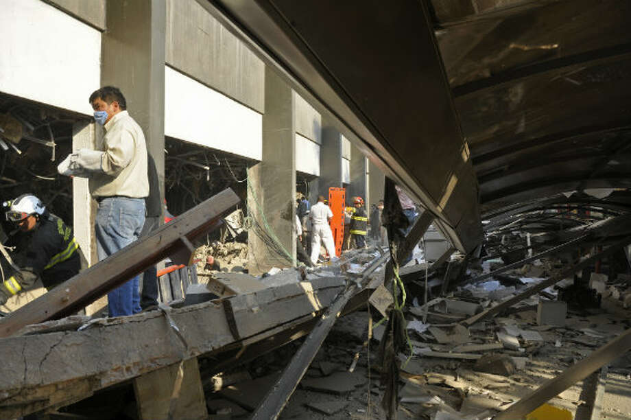 Firefighters belonging to the Tacubaya sector and workers dig for survivors after an explosion at a building adjacent to the executive tower of Mexico's state-owned oil company PEMEX, in Mexico City, Thursday Jan. 31, 2013.