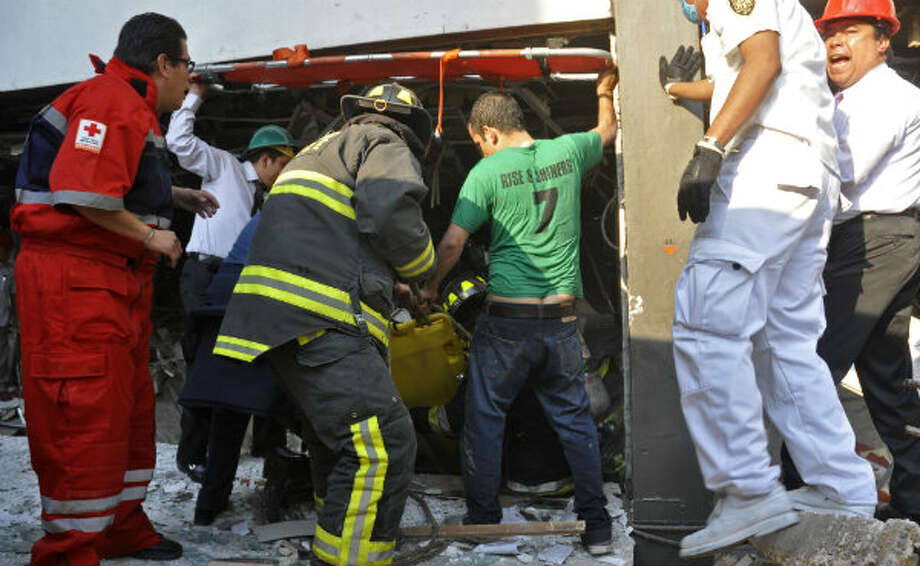 Firefighters belonging to the Tacubaya sector and emergency responders pull out a survivor after an explosion at an adjacent building to the executive tower of Mexico's state-owned oil company PEMEX, in Mexico City, Thursday Jan. 31, 2013.