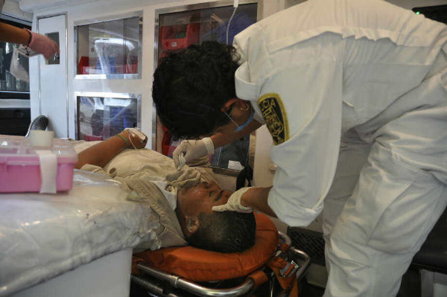 An emergency worker treats an injured worker of Mexico's state-owned oil company PEMEX after an explosion at an adjacent building to the executive tower of PEMEX in Mexico City, Thursday Jan. 31, 2013.