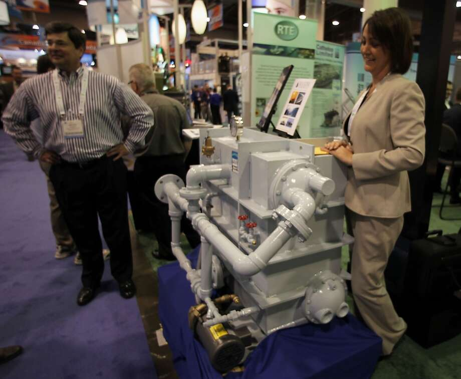 Maxim Evaporators' Monica Rogers right, stands with one of the companies model HJ50C heat recovery evaporator during OTC 2013 at Reliant Park Tuesday, May 7, 2013, in Houston. ( James Nielsen / Houston Chronicle ) Photo: James Nielsen, Houston Chronicle
