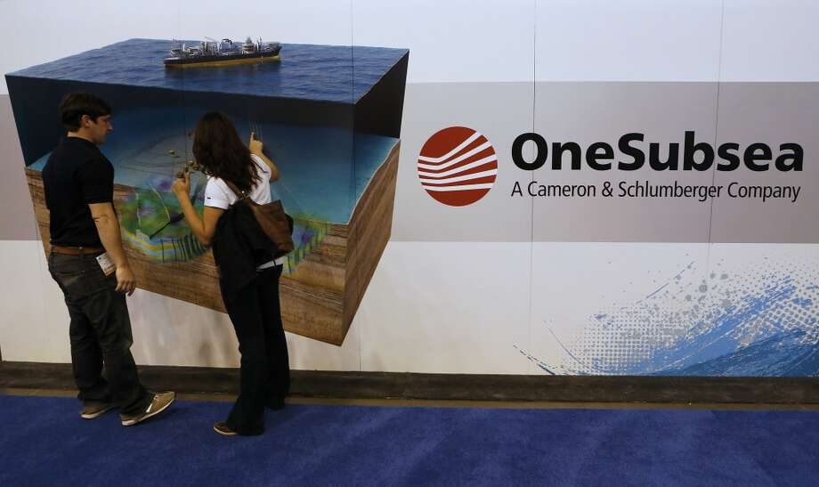 Attendees view OneSubsea signage during the 2013 Offshore Technology Conference (OTC) in Houston, Texas, U.S., on Tuesday, May 7, 2013. The Offshore Technology Conference (OTC) is organized and operated to promote and further the advance of scientific and technical knowledge of offshore resources and environmental matters. Photographer: Aaron M. Sprecher/Bloomberg Photo: Aaron M. Sprecher, Bloomberg
