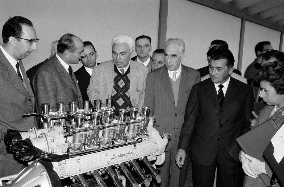 The introduction of the new Lamborghini 350GTV at the Lamborghini Factory, Sant? Agata, October 1963. A group of pleased visitors stand next to a display version of the new Lamborghini V12 motor. The man with the white hair and the tartan sweater is the famous Italian driver PieroTaruffi.
