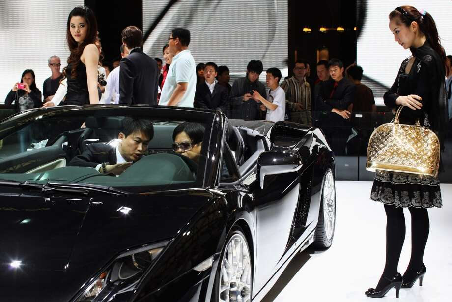 A sales person (L) introduces a Lamborghini sport car to a Chinese man in the closed section during a special trade visitors opening of the Auto Shanghai 2009 at Shanghai New International Expo Center on April 23, 2009 in Shanghai, China.