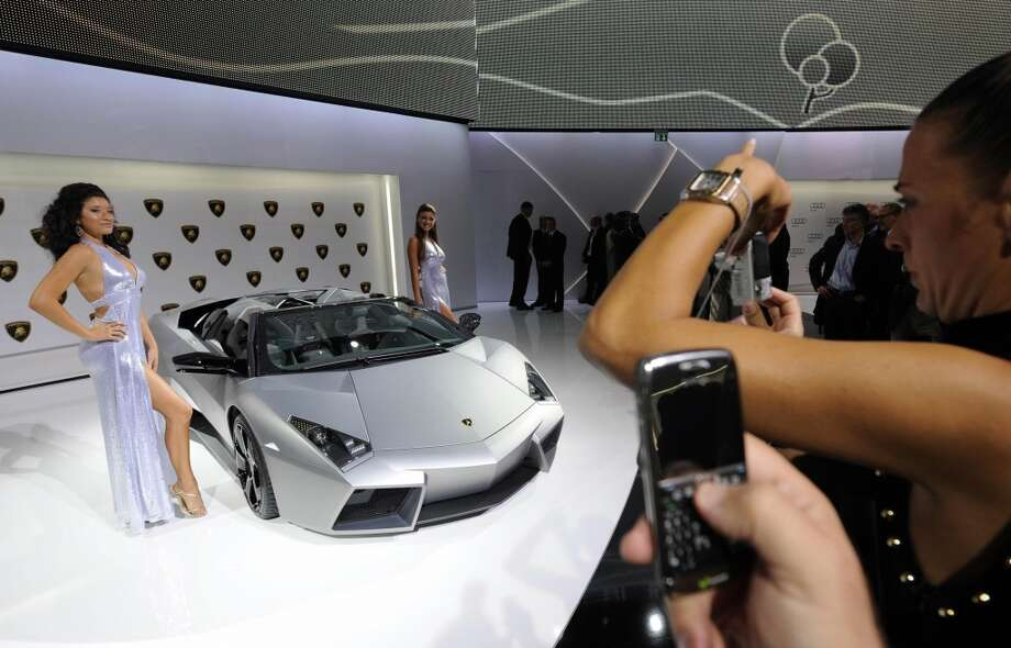 Hostesses pose beside a Lamborghini Reventon ahead of the 63rd International Motor Show (IAA) in the central German city of Frankfurt am Main on September 14, 2009.