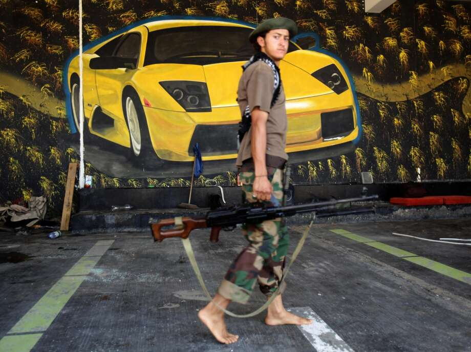 A Libyan rebel walks past a painting of a Lamborgini at the seaside rest house of Saadi Kadhafi, a son of Libyan leader Moamer Kadhafi, in Tripoli on August 26, 2011.
