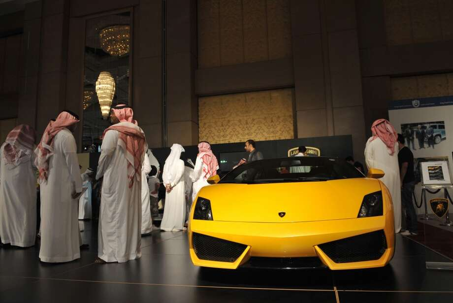 Saudi men inspect a Lamborghini at a luxury auto show in Riyadh, late on October 10, 2011.