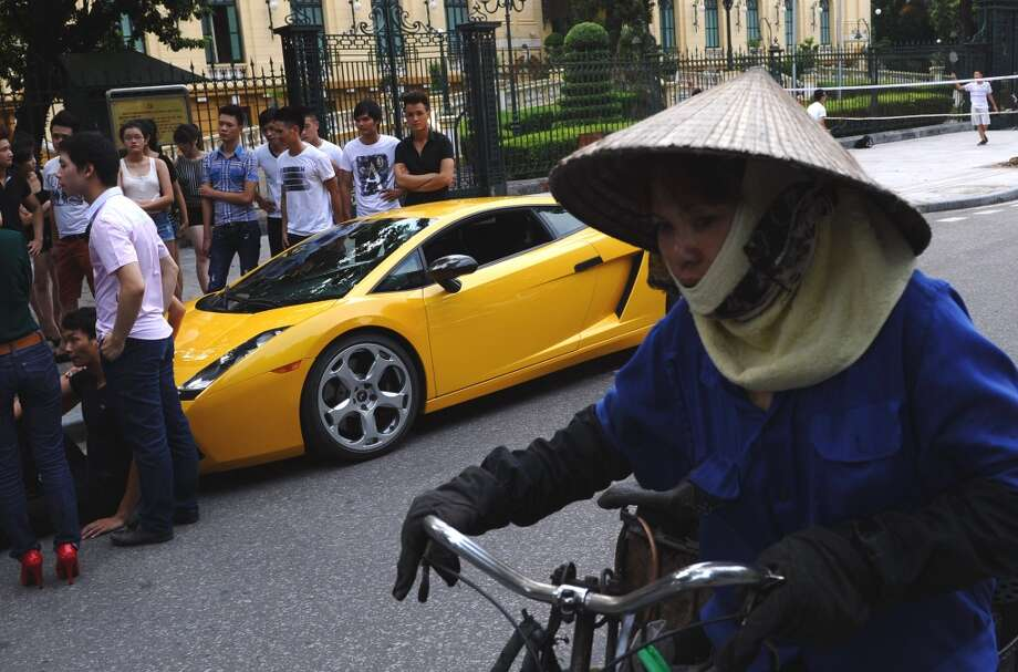 A coal bricks vendor rides past a Lamborghini car in downtown Hanoi on July 6, 2012.