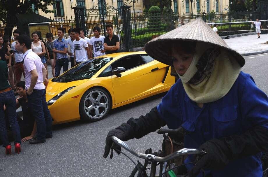 A coal bricks vendor rides past a Lamborghini car in downtown Hanoi on July 6, 2012.