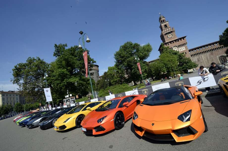 Lamborghini sports are parked on May 7, 2013 in front of Milan's Sforza castle in Milan on the eve of the first leg of a 1,200km Grand Tour through Italy to mark the 50th anniversary of the carmaker. Over 1,200 km of Italian countryside will form the backdrop for hundreds of Lamborghinis, from unforgettable historic GTs to the latest futuristic supercars, which will arrive from every part of the globe and parade through the most beautiful cities in Italy until May 11 when they will reach their final destination, Bologna.