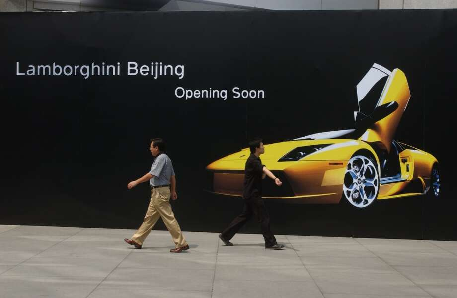 Pedestrians walk by a billboard for Lamborghini's new Beijing showroom at a shopping center July 27, 2004 in Beijing.  China has the world's third largest auto market in the world. Many foreign luxury brand companies are making their way into the mainland even though only about one percent of the population presently can afford their goods.