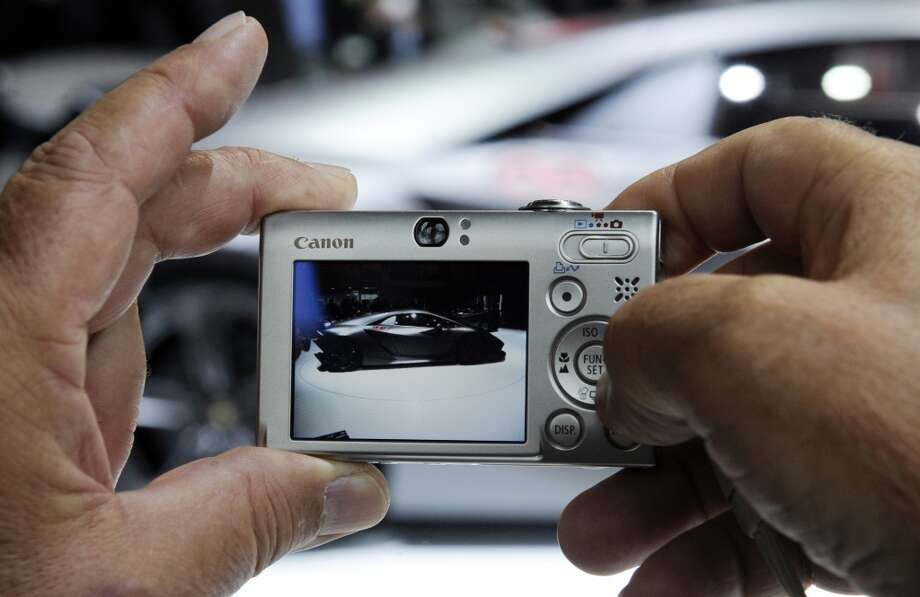 A man takes a picture of a Lamborghini presented at Paris Auto Show on October 1st, 2010, on the event's opening day.