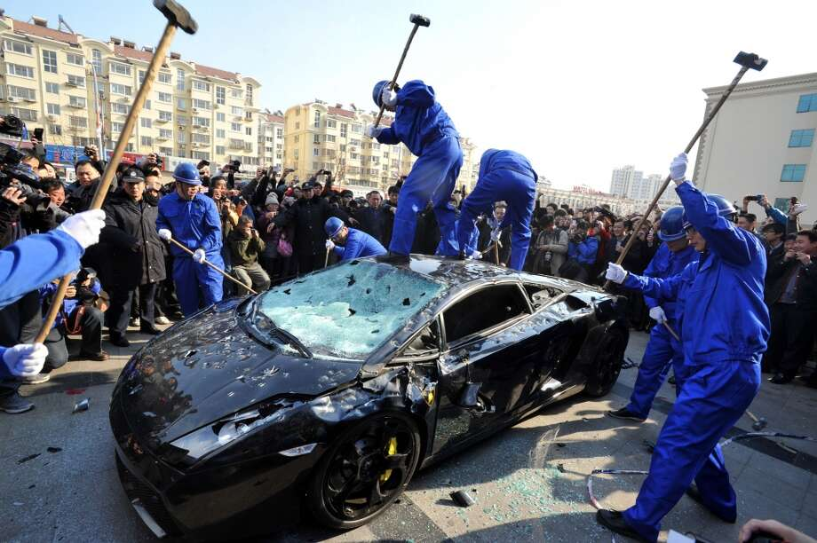 Workers destroy a Lamborghini Gallardo L140 luxury sports car to mark World Consumer Rights Day in Qingdao, eastern China's Shandong province on March 15, 2011. The car's owner hired people to publicly destroy the vehicle when it failed to function after a service by an official Lamborghini service station. The protest was made to provoke public support and goad the manufacturer to respect his consumer rights.