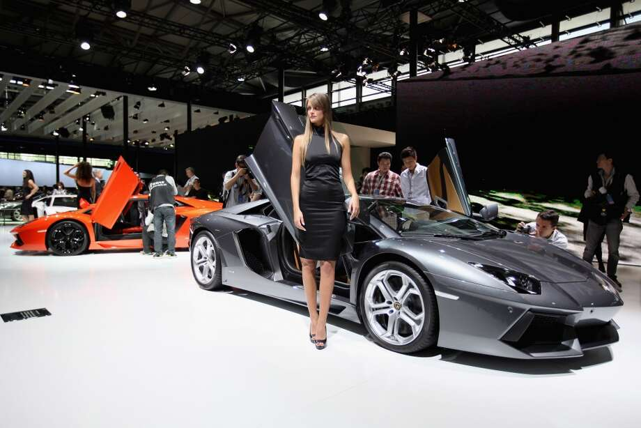 A model stands beside the Lamborghini Aventador LP700-4 sport car during the media day of the Shanghai International Automobile Industry Exhibition at Shanghai New International Expo Center on April 19, 2011 in Shanghai.