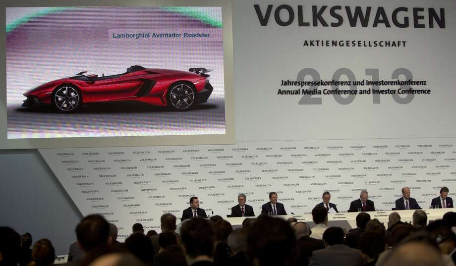 Members of the board of German carmaker Volkswagen attend the company's annual press conference on March 14, 2013 in Wolfsburg, northern Germany, while an overhead screen displays an image of a Lamborghini Aventador Roadster.