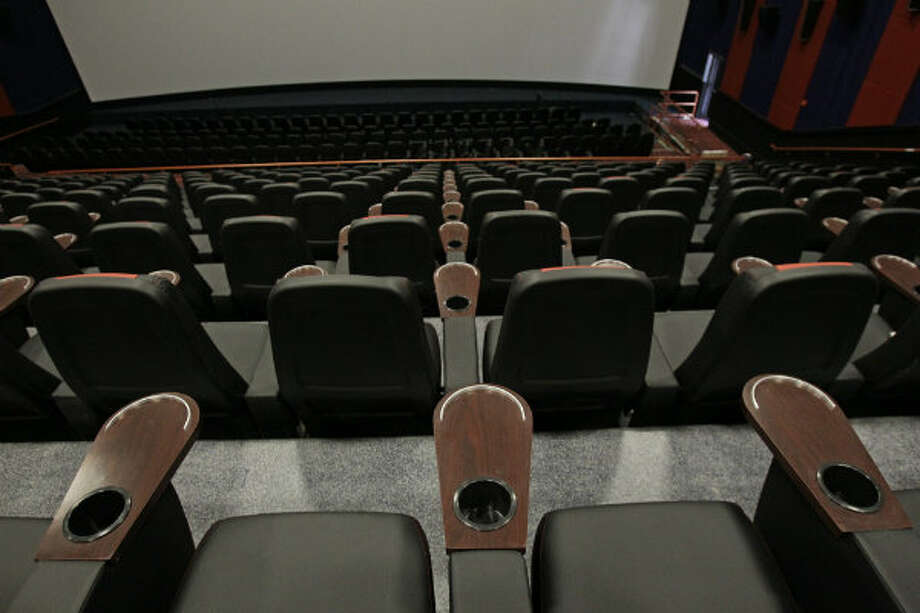 Rocking theater seats have cup holders and room for popcorn or candy.