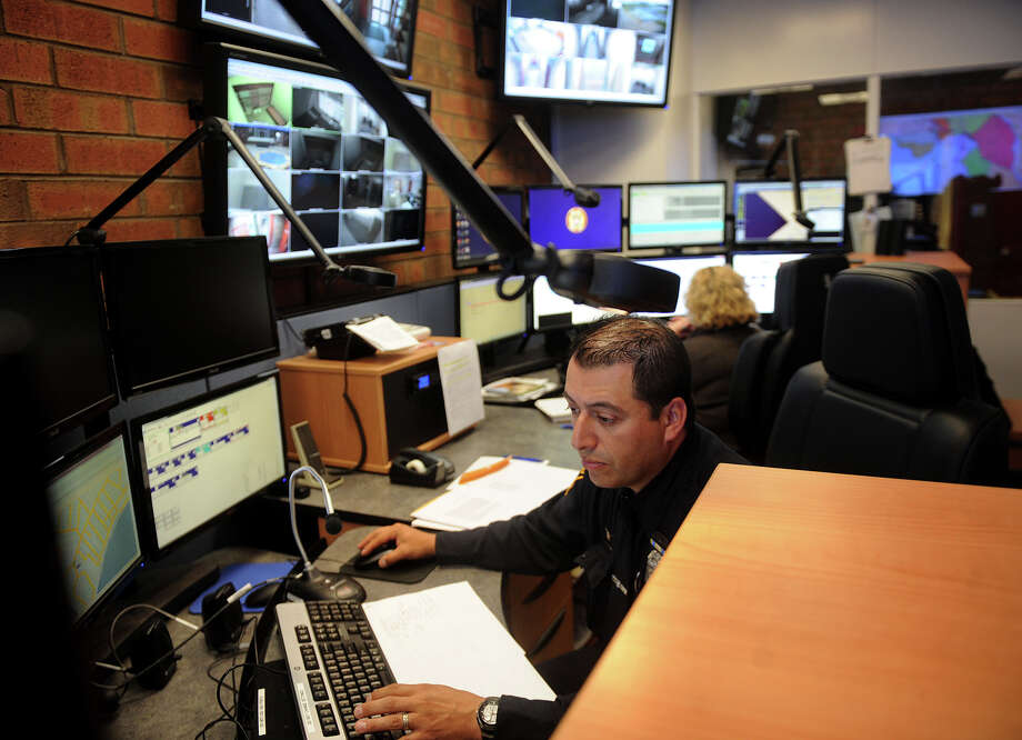 Officer William Ospina, left, works in the new, combined fire and police dispatch center at Police Department Headquarters in Milford, Conn. on Wednesday, May 8, 2013. Photo: Brian A. Pounds / Connecticut Post