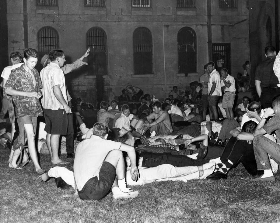 04/29/1961 - Youths, mostly college students, picked up and taken to jail after a near-riot during Splash Day activities on Galveston Island. The Galveston jail was too crowded so prisoners were kept outside. The students milled around in the courtyard surrounded by a high fence.