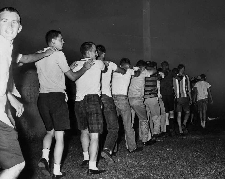 04/29/1961 - Youths, mostly college students, picked up and taken to jail after a near-riot during Splash Day activities on Galveston Island. Arrested students are marched into the Galveston Jail courtyard. They were processed in the jail and returned to the yard.
