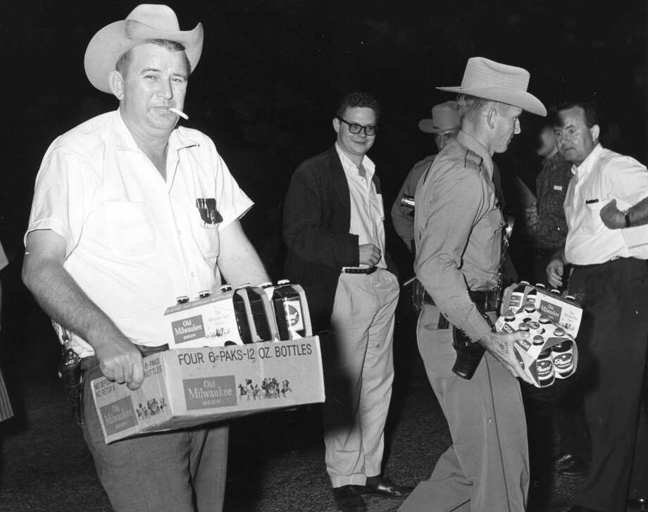 04/29/1961 - Law enforcement officers confiscate beer from youth who were picked up and taken to jail after a near-riot during Splash Day activities on Galveston Island.