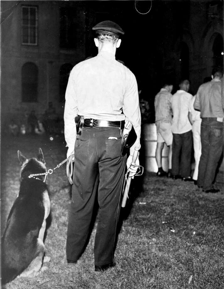 Officer and his police dog on guard duty. Arrested students filled jail and the jail grounds. Published April 30, 1961.